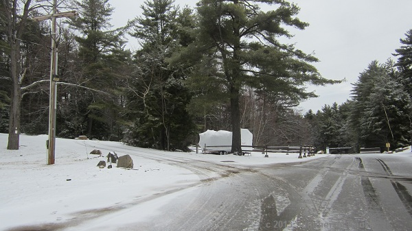 The service road behind the main lodge at Gunstock Recreation area leads to a gate.  The tree at the far left of the photo has a white blaze and sign, follow the road left past the tree and then to the left.